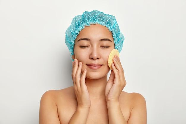 魅力的なアジアの女性の写真は、化粧用スポンジで顔を洗い、顔をクレンジングし、トップレスで立ち、目を閉じて、青いバスキャップを着用します