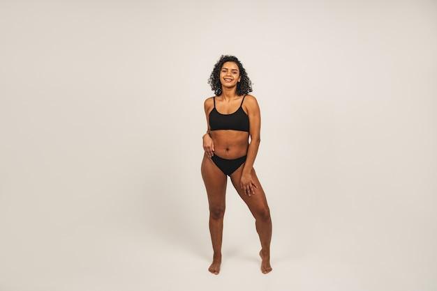 매력적인 흑인 여성의 사진은 검은 속옷을 입는다. 흰색 배경 위에 격리.