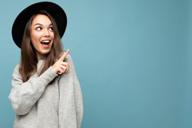 매력적인 갈색 머리 행복 즐거운 젊은 여자 가리키는 손가락의 사진
