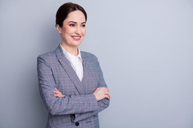 Фото привлекательной бизнес-леди, скрестив руки, хорошее настроение, опытный опытный учитель, профессия, взгляд, пустое пространство, заинтересованный, носить клетчатый пиджак, белая рубашка, изолированный серый цвет фона