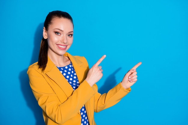 매력적인 비즈니스 여성의 성공적인 작업자 직접 손가락 측면 빈 공간 쇼 참신 제품 관리자의 사진은 노란색 블레이저 정장 점선 블라우스 셔츠 고립 된 파란색 배경을 착용