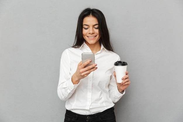 灰色の背景で隔離の手で携帯電話とテイクアウトのコーヒーを保持しているフォーマルな服装で魅力的なビジネス女性の写真