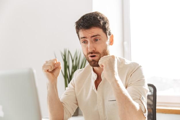 Фотография привлекательного бизнесмена 30-х годов в белой рубашке, использующего ноутбук, во время работы в ярком офисе