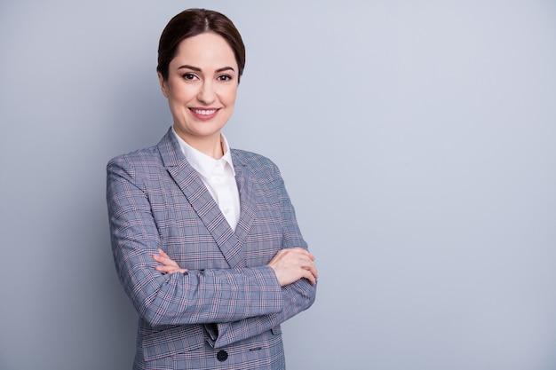 Фото привлекательной очаровательной уверенной бизнес-леди, скрестив руки, сияющая улыбка, хорошее настроение, опытный учитель, занятие, носить клетчатый пиджак, белая рубашка, изолированный серый цвет фона