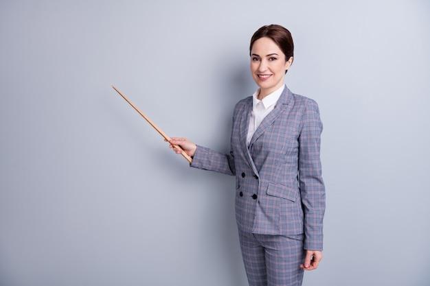 Фото привлекательной жизнерадостной леди хорошее настроение преподаватель профессии онлайн-урок в интернете показывает указатель пустого места новый объект темы носить клетчатый костюм изолированный серый цвет фона
