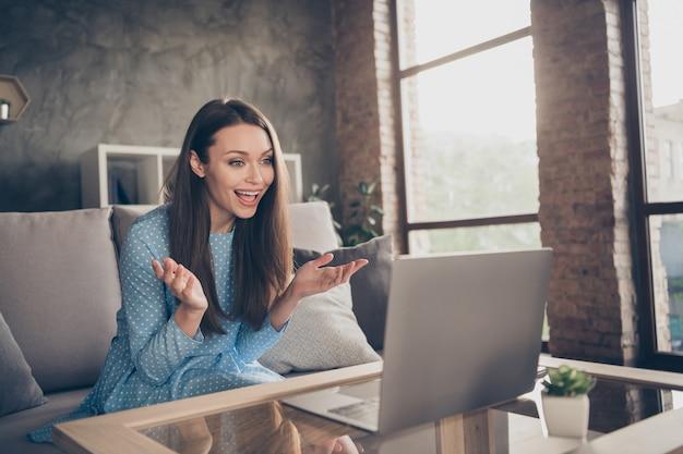 매력적인 쾌활한 여성의 사진 스카이프 노트북 온라인 화상 통화 날짜는 남자 친구에게 뉴스 인터넷 회의 검역소에 집에 앉아 소파에 세련된 점선 드레스를 입고 실내에 있다고 이야기합니다.