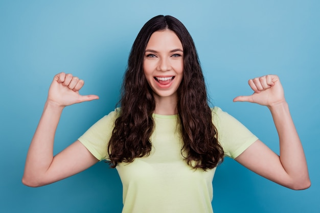 파란색 배경을 자랑하는 매력적인 쾌활한 자신감 있는 소녀의 사진