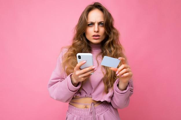 분홍색으로 격리된 분홍색 옷을 입은 매력적인 집중된 젊은 금발 곱슬머리 여성의 사진
