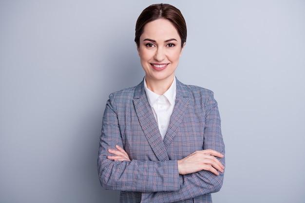 Фото привлекательной уверенно бизнес-леди скрещенными руками сияющая улыбка хорошее настроение квалифицированный учитель профессия профессия носить клетчатый пиджак белая рубашка изолированный серый цвет фона