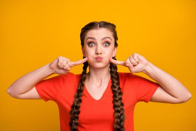魅力的な狂気の女性の写真は、エアプレスの指の頬でいっぱいの息の口を保持します
