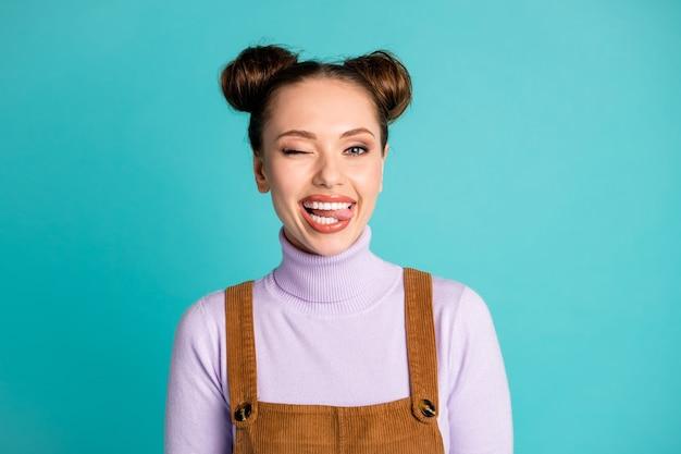 매력적인 귀여운 요염한 여성 여자 친구 여자 바람둥이 남자 친구 눈 깜박임 눈이 튀어나와 혀 두 개의 사랑스러운 롤빵 보라색 스웨터 갈색 전체적으로 고립 된 청록색 배경의 사진