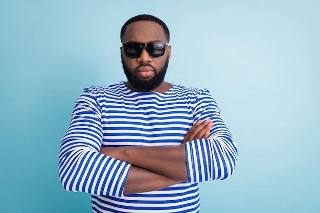 Фото привлекательного темнокожего парня, скрестив руки, не улыбаясь, строго выглядящих путешественников, пляжный контроль над морем, носить солнцезащитные очки, полосатую рубашку моряка, изолированную синюю стену