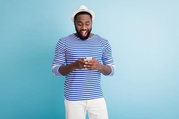 魅力的なダークスキンの男の旅行者の良い気分の写真は、電話アプリのブラウジングチャットの友人が白い日よけ帽の縞模様のセーラーシャツのショートパンツを着用し、青い色の壁を分離しました
