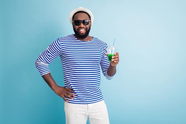 魅力的なダークスキンの男の旅行者プールパーティーの写真は、緑のアルコール飲料カップを保持します良い気分着用太陽の仕様白いサンキャップストライプセーラーシャツショーツ孤立した青い色の壁