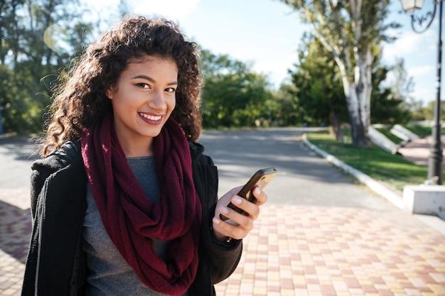 Фото болтающей привлекательной темнокожей дамы в свитере и шарфе