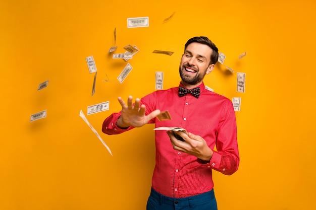 Фото привлекательного элегантного забавного парня с веером, деньги, баксы, тратящие джекпот, выбрасывание денег, падающая одежда, модная красная рубашка с галстуком-бабочкой