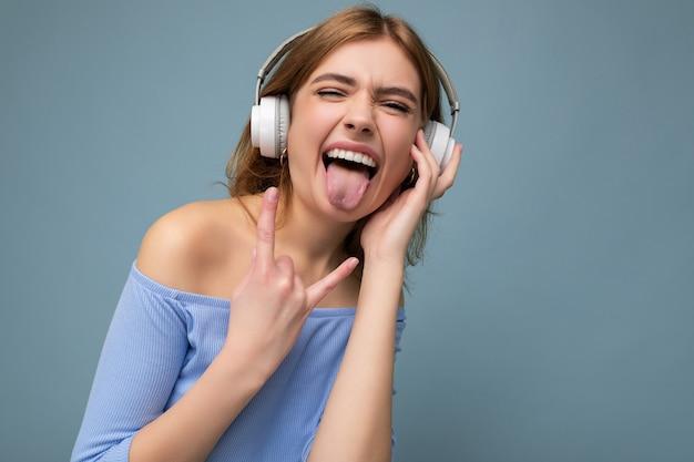 青いクロップトップを着ている魅力的な感情的な若いブロンドの女性の写真