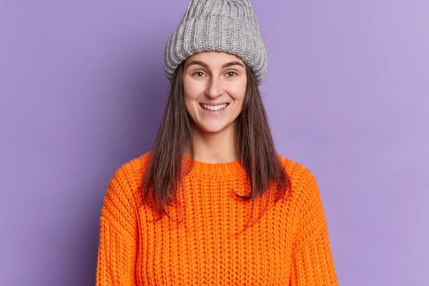 Фотография привлекательной европейской женщины с длинными темными волосами, приятной улыбкой, счастливой зимним праздникам, носит оранжевый вязаный свитер и шляпу.
