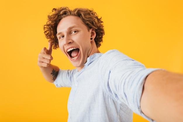 黄色の背景の上に分離された、自分撮り写真を撮り、カメラに指を指している魅力的な興奮した男の写真