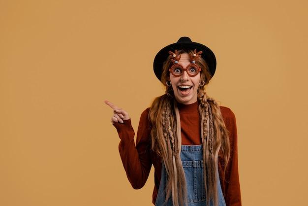 Фотография привлекательной женщины-фермера стоит и улыбается, носит забавные очки и указывает слева. белая женщина носит джинсовый комбинезон и шляпу изолировал коричневый цвет фона.