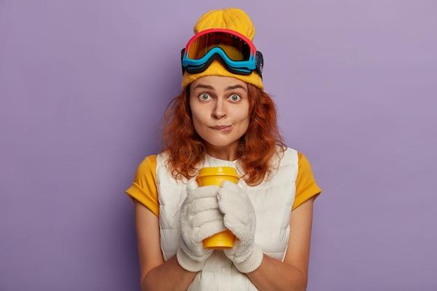 매력적인 여성 모델의 사진에는 생강 머리카락이 있고 입술을 물고 양손으로 테이크 아웃 컵을 들고 카메라를 직접 바라보고 조끼가 달린 노란색 티셔츠를 입습니다.