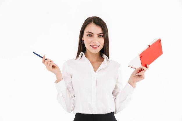 白い壁に隔離されたオフィスで働いている間、日プランナーを保持するフォーマルな服を着た魅力的な女性労働者の実業家の写真