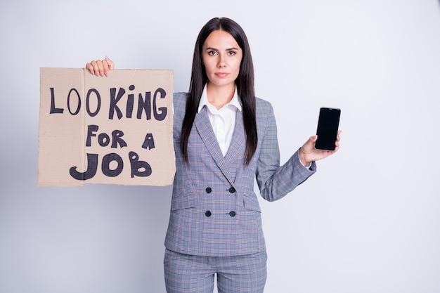 Фотография привлекательной уволенной расстроенной дамы-менеджера, держащей телефонный картонный плакат, ищите работу, готовьте гаджет для приема звонка, собеседования, хотите, чтобы формальная одежда, клетчатый костюм, изолированный серый цвет фона