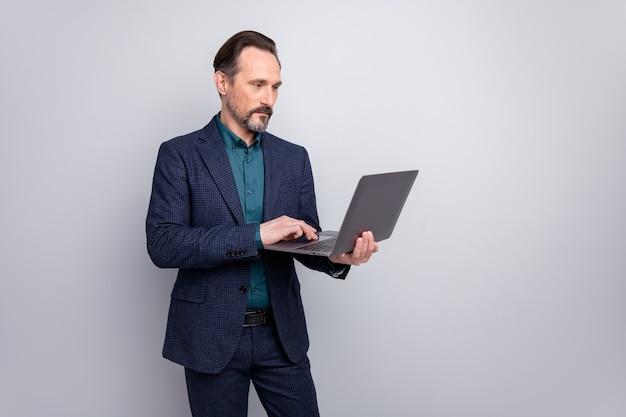Netbook을 들고 매력적인 집중된 비즈니스 남자의 사진