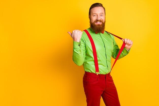 Фото привлекательного забавного парня, крутого фанк-взгляда, указывающего на большой палец, пустое пространство, распродажа, одежда для покупок, зеленая рубашка, красный галстук-бабочка, подтяжки, брюки, изолированные яркие цвета