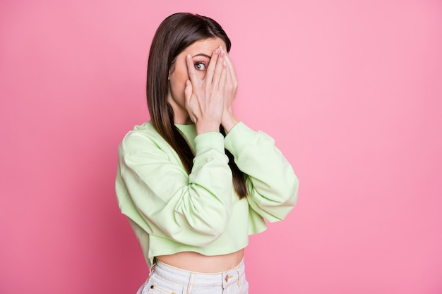 눈을 감고 눈을 감고 있는 매력적인 여성의 사진은 비밀스러운 호기심 많은 사람이 캐주얼한 녹색 작물 스웨터 풀오버를 입고 분리된 분홍색 파스텔 색상 배경을 알고 싶어합니다.