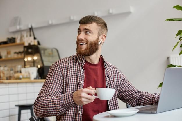 カフェに座って、コーヒーを飲み、基本的な服を着て、振り返りながら、ラップトップで働いている魅力的な生姜ひげを生やした男の写真、素晴らしいコーヒーをバリスタに感謝します。