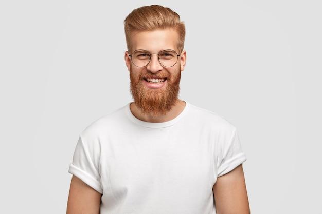 만족스러운 표정으로 매력적인 생강 남자의 사진은 두꺼운 수염을 가지고 있습니다.