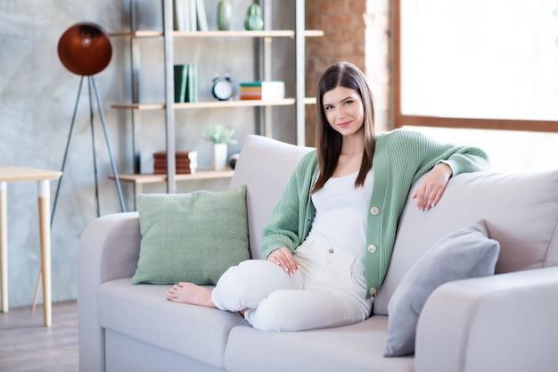 フラットハウスのソファに座っている魅力的な女の子の写真