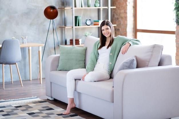 ライトフラットハウスアパートのソファに座っている魅力的な女の子の写真