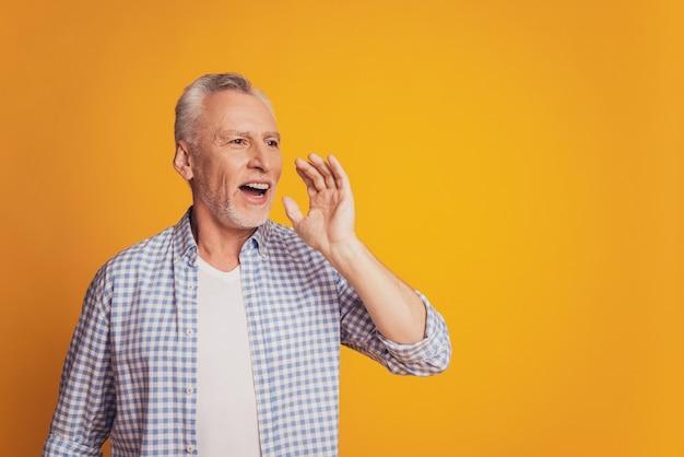 魅力的なおじいちゃんの写真が口の近くの空きスペースの手を叫ぶ共有の秘密