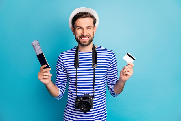 Фотография привлекательного парня, фотографа, держите профессиональный цифровой фотоаппарат, путешественник, покупающий билеты с помощью кредитной карты, носите полосатую матросскую рубашку, жилет, кепку изолированного синего цвета