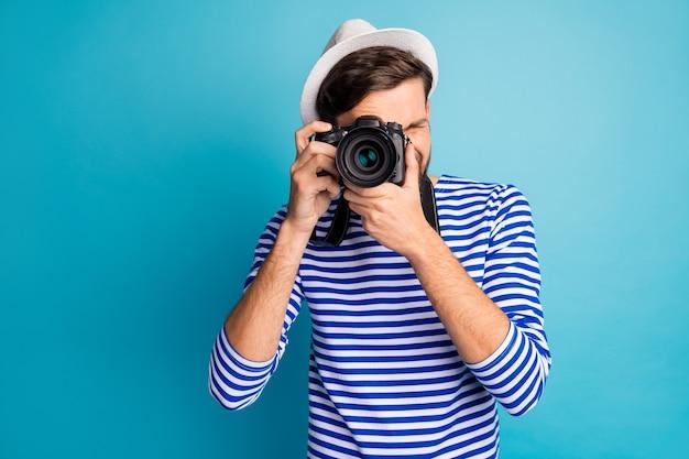 매력적인 남자 사진 작가의 사진 보유 전문 디지털 렌즈 카메라 여행자 사진보기 사진 착용 스트라이프 선원 셔츠 조끼 흰색 모자 절연 파란색