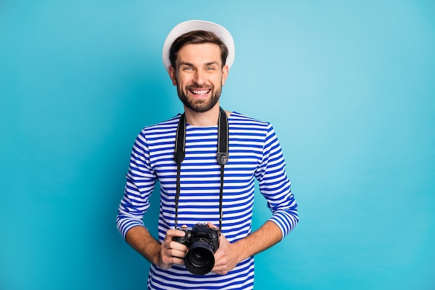 매력적인 남자 사진 작가의 사진은 해외 여행 전문 디지털 렌즈 카메라를 잡아 사진을 스트라이프 선원 셔츠 조끼 흰색 모자 절연 파란색을 착용합니다