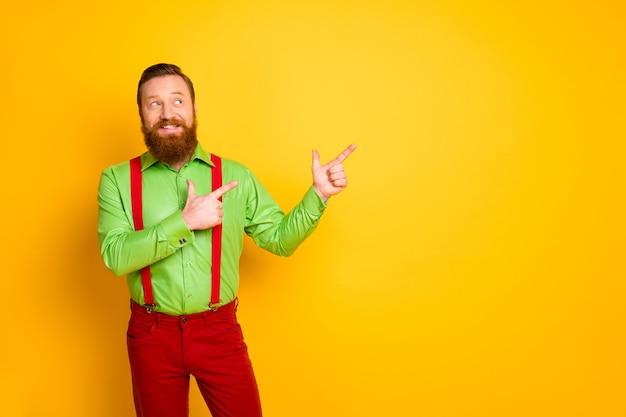 Фотография привлекательного парня-хипстера указывает пальцем на пустое пространство, советуя цены в сезон покупок в черную пятницу носить зеленую рубашку красные подтяжки брюки изолированные желтый цвет