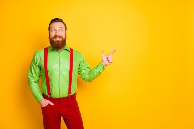 매력적인 힙 스터 남자의 사진은 검은 금요일 쇼핑 시즌 오프닝 착용 녹색 셔츠 빨간 멜빵 바지 절연 밝은 색상을 제시 손가락 빈 공간을 나타냅니다