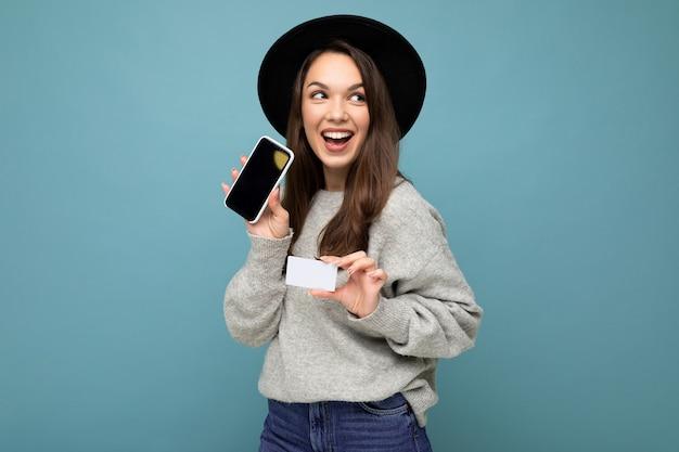 검은 모자와 회색 스웨터를 입고 매력적인 즐거운 젊은 갈색 머리 여자의 사진