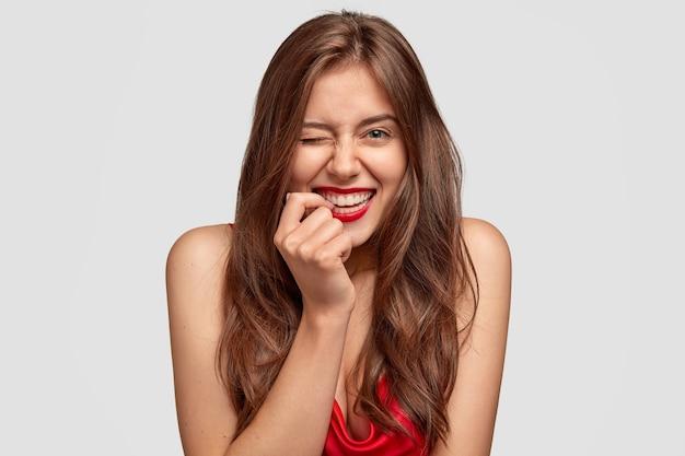 매력적인 여성의 사진은 남자 친구와 바람을 피우고, 눈을 깜박이며, 앞쪽 손가락을 붉은 입술 근처에 유지하고, 긍정적으로 미소 짓습니다.