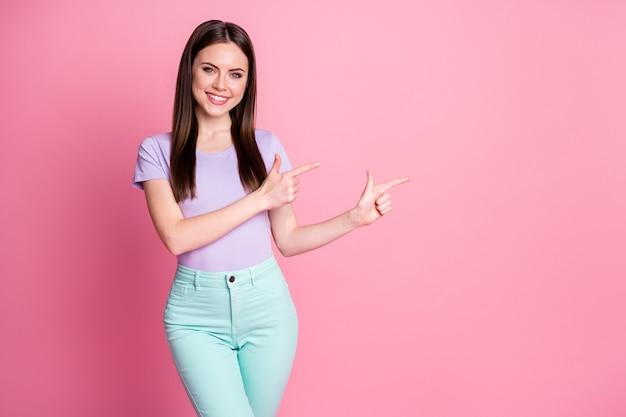 魅力的な女性の良い気分の写真直接指側空のスペースデモンストレーションノベルティバナー販売ショッピングウェアカジュアルバイオレットtシャツティールパンツ孤立したピンクのパステルカラーの背景