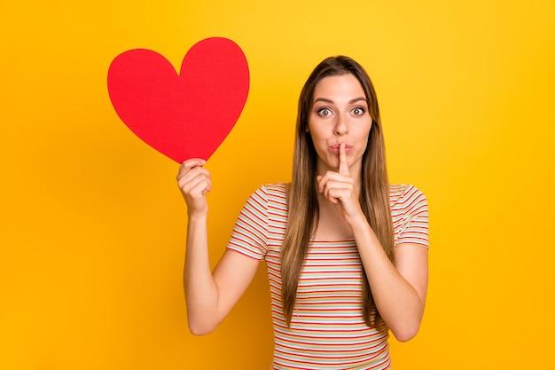 Фотография привлекательной женщины, держащей большое красное бумажное сердце, приглашение на свидание для парня, держащего палец во рту, секретный сюрприз, повседневная полосатая футболка, изолированная на стене желтого цвета