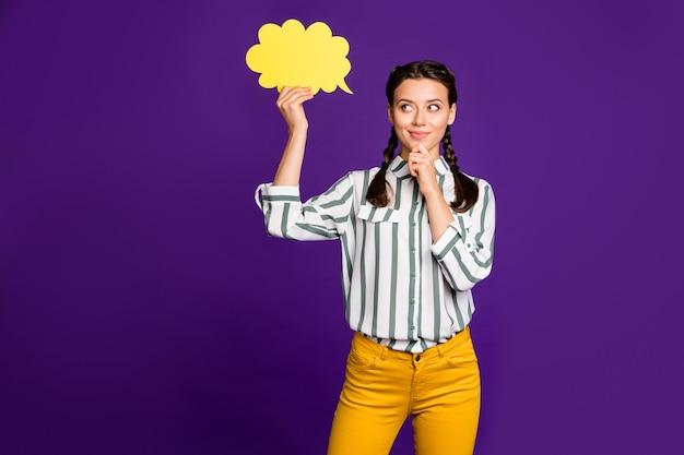 Фото привлекательной леди держать бумагу облако разума подумать над творческим диалогом ответ рука на подбородке носить полосатую рубашку желтые брюки изолированный фиолетовый цвет фона