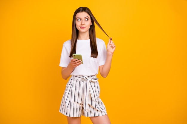 매력적인 여자의 사진 전화 손을 잡고 빈 공간이 손가락 주위에 컬을 상처 입고 캐주얼 흰색 티셔츠 스트라이프 여름 반바지 절연 생생한 노란색 벽