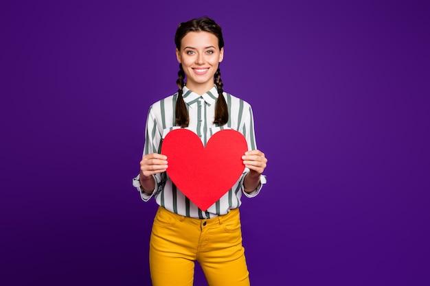 Фотография привлекательной женщины с большим красным бумажным сердцем, празднующей день святого валентина, приглашающей парня на свидание, носить полосатую рубашку желтые брюки, изолированные на фиолетовом цветном фоне
