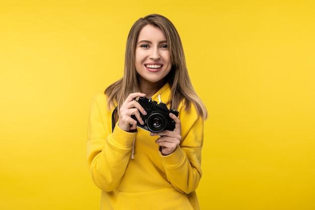 魅力的な女性の写真は笑顔でカメラを持って写真を作りたいです。カジュアルな黄色のフーディ、孤立した黄色の背景を着ています。