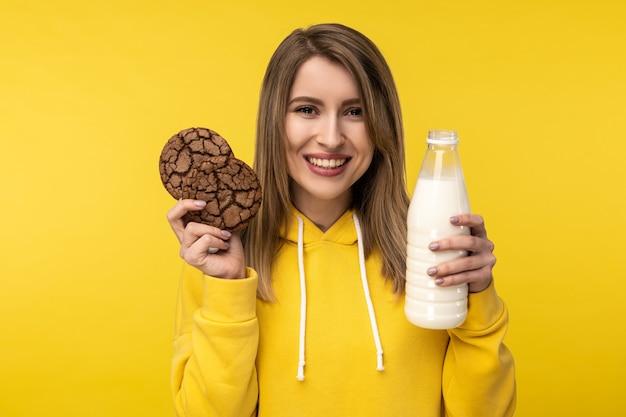 Фотография привлекательной дамы держит печенье и молоко, хорошо относится к молочным продуктам. носит повседневную желтую толстовку с капюшоном на изолированном желтом фоне.