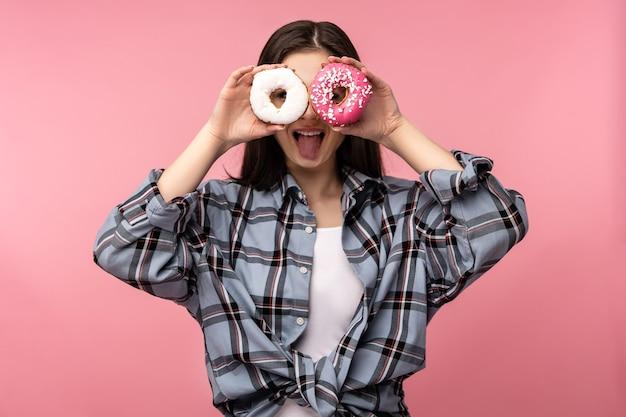 매력적인 숙 녀의 사진 보유 도넛 사탕 달콤한 음식 착용 미소 행복 캐주얼 체크 무늬 셔츠 흰색 땀 받이 격리 된 분홍색 배경에 의해 덮여 눈.